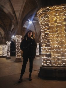 Girl standing next to Gothic columns wrapped in white lights.
