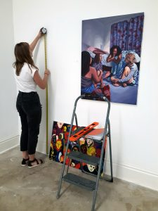 Student hanging artwork in a gallery.
