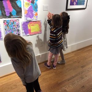 Three children look at art hanging on a gallery wall.