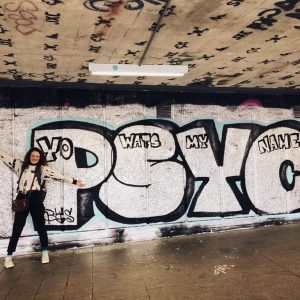 Girl posing next to graffiti art painted on wall.