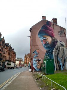 Mural of a man looking at a bird pirched on his finger, painted on the side of a four-story apartment house in Glasgow, Scotland.
