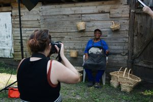 A student taking a photo of a basket weaver sitting against a workshed.