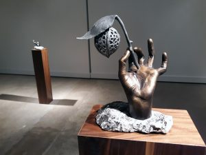 bronze sculpture of a hand holding a twig with nut and leaf