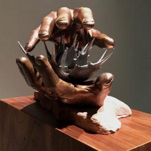 bronze sculpture of two hands around spiked flower