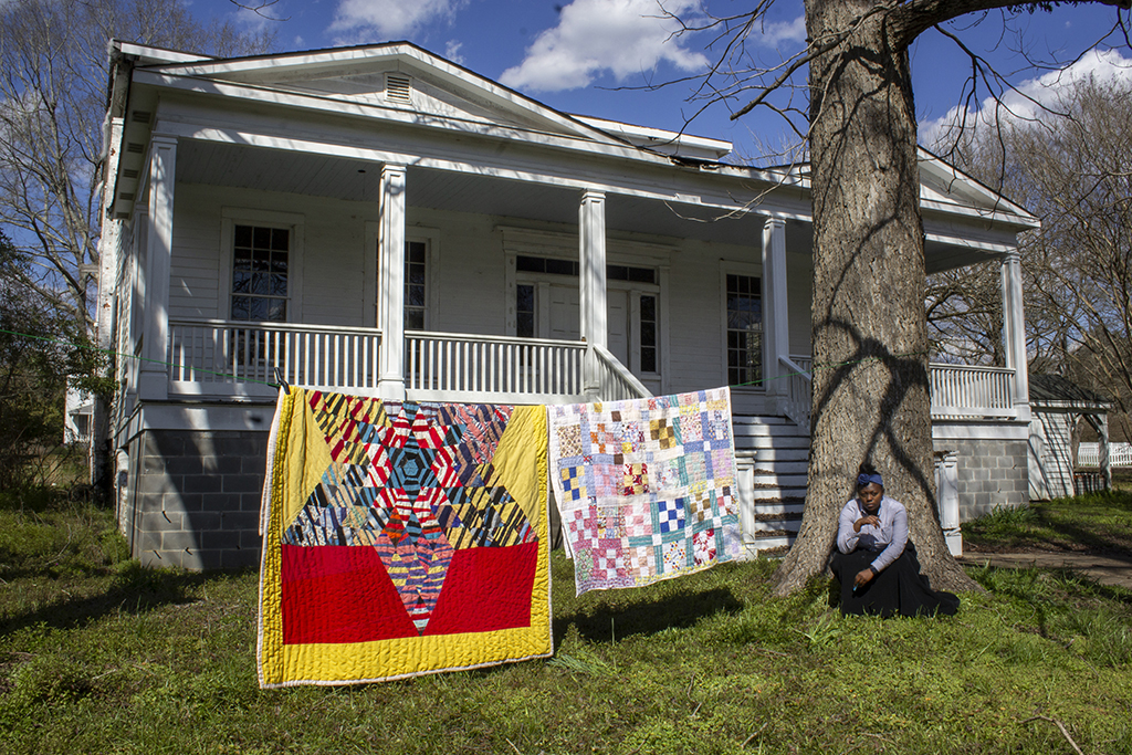 An African American woman seated against a large tree, beside two quilts hanging on a clothesline in front of house.