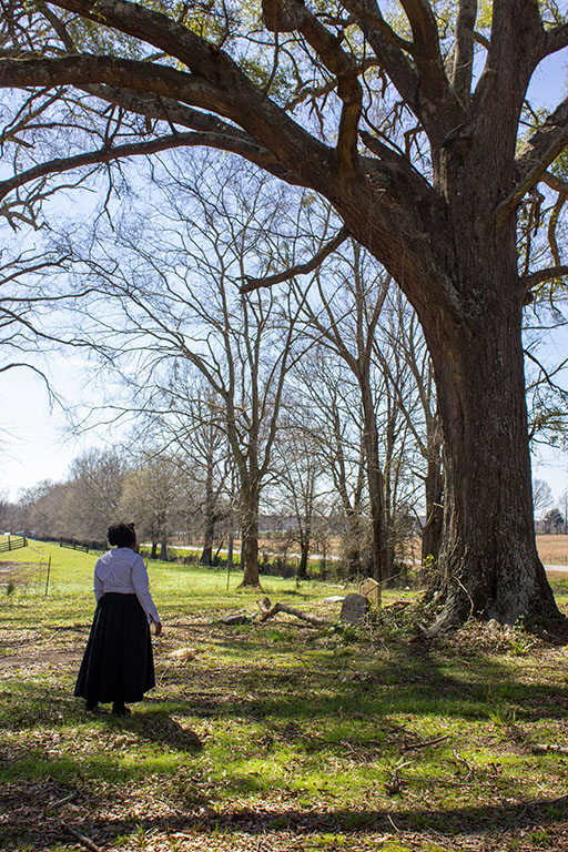 photo of an African American woman in a long dress standing at old gravestones.