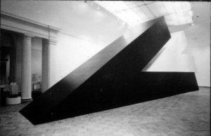large black Minimalist sculpture, installed indoors