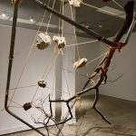 Abstract sculpture of scrap metal, wood, rocks and cording by Molly Lay