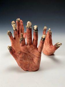 three ceramic hands reaching upward by Sandra Vega