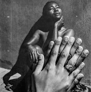 photo of two hands covering the image of a woman in a photograph.