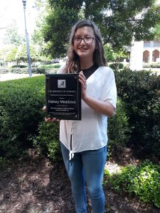 Student holding an award plaque, under the trees.