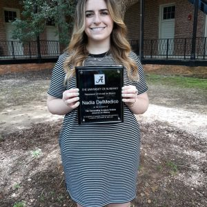 Student holding an award plaque, underneath a tree.